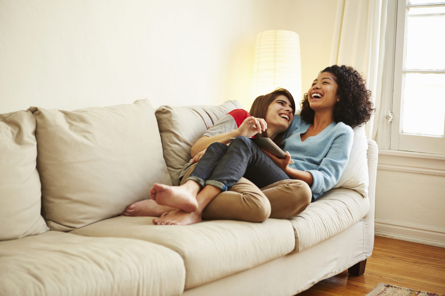 Caucasian Pregnant Lesbian Couple Relaxing On Sofa Stock Image